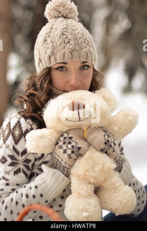 Beautiful,nice,smiling,little,attractive,wearing sweater,hut,mittens,girl with a fluffy,soft,beige,white,teddy bear,cute - Stock Photo
