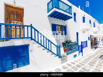 Mykonos old town street with cobbled walkways, white walls, and painted door and windows, Mykonos island, Greece - Stock Photo