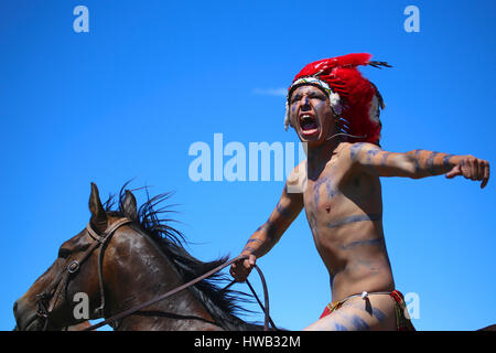 Native American Indian wearing blue war paint and wearing red feather ceremonial head dress Crazy Horse reenactor - Stock Photo
