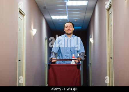 Young handsome pushing cleaning cart - a series of HOTEL images. - Stock Photo