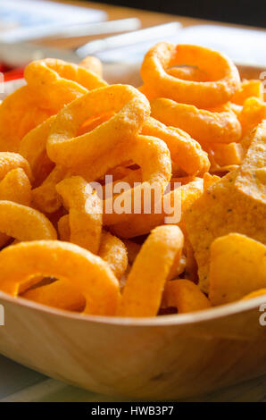 A closeup of a bowl of onion ring and tortilla crisps. - Stock Photo