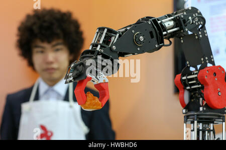 Hanover, Germany. 20th Mar, 2017. A robot on the Tensor Flow stand puts a portion of sushi on a plate at the CeBIT - Stock Photo