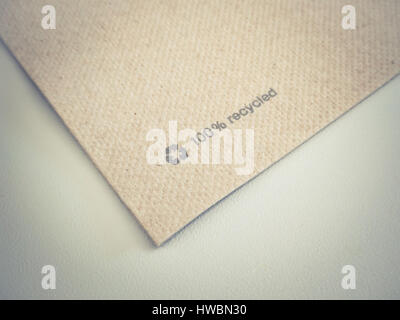 Close up shot of some recycled paper with recycle symbol. - Stock Photo