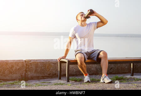 young strong Caucasian man with white headphones drinks a protein cocktail from a shaker after running on open air. - Stock Photo
