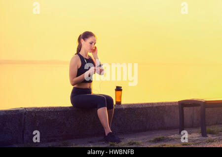Slender  sports girl near the river resting after workout outdoors. Listens to music on the smartphone at sunset. - Stock Photo