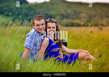 Cheerful,beautiful,smiling happy couple,young family on date.Happy,young couple watching sunset on green sunny meadow.Happy,cheerful,smiling - Stock Photo