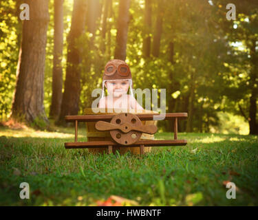 A little baby is sitting in a wooden airplane basket prop in the park pretending to travel and fly with a pilot - Stock Photo
