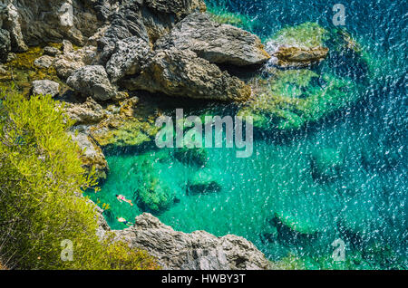 Tourists shorkling between Rocks in Azure Bay of Beautiful Paleokastritsa in Corfu Island, Greece - Stock Photo