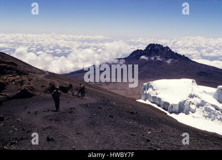 Climbers starting the descent from the top of Mount Kilimanjaro the highest point in Africa with 5895 meters above - Stock Photo