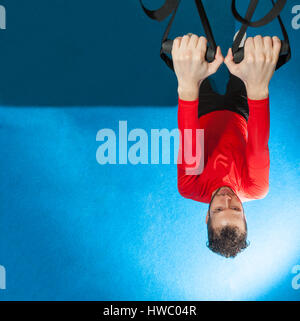 one white curly-haired, bearded sporty man exercising suspension push-up with fitness trx straps in gym - Stock Photo