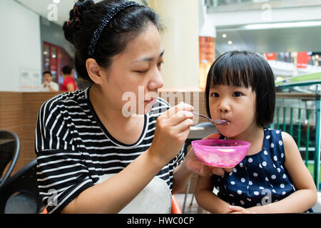 Asian Mother Feeding Her Daughter in Outdoor Cafe - Stock Photo