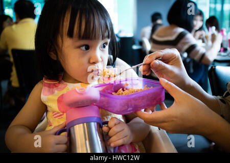 Asian Mother Feeding Kid Daughter Food in a Restaurant - Stock Photo