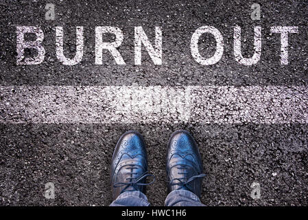 Word burn out written on asphalt with legs and shoes, burn out concept - Stock Photo
