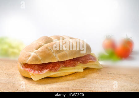 inviting sandwich with salami and cheese on wooden desk with blurred foggy tomatos and lettuce background - Stock Photo