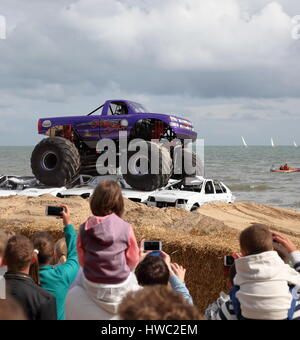 Spectators look on as Slingshot Monster truck crushes cars stacked in sand at 2014 Wheels Festival, Bournemouth - Stock Photo