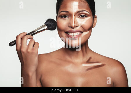 Close up portrait of beautiful young woman applying makeup on her face with highlight and shading. Pretty woman - Stock Photo