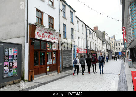 View of 5 young men walking past Five Guys fast food restaurant on Caroline Street in Cardiff City Centre, Wales - Stock Photo