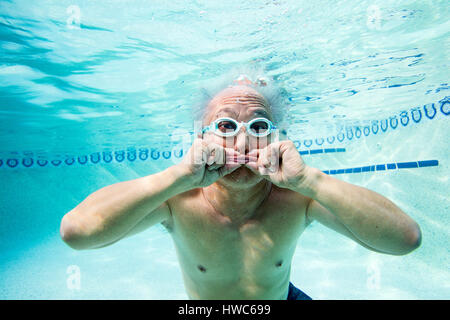 Senior being silly underwater in a swimming pool - Stock Photo