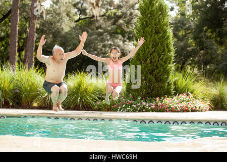 Grandfather swims in the pool with his grandaughter - Stock Photo