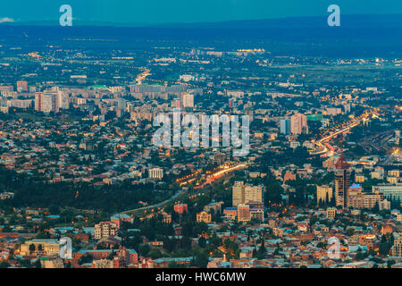 Tbilisi, Georgia. Aerial Panoramic View Of Evening City In Light llumination. Residential Districts In Summer Blue - Stock Photo