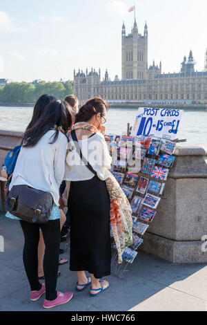 People buying postcards for sale by the River Thames in London, England, UK - Stock Photo
