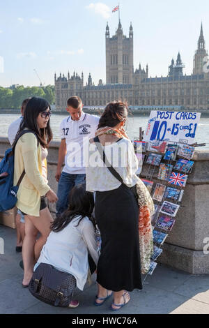 Young tourists choosing postcards for sale by the River Thames in London, England, UK - Stock Photo