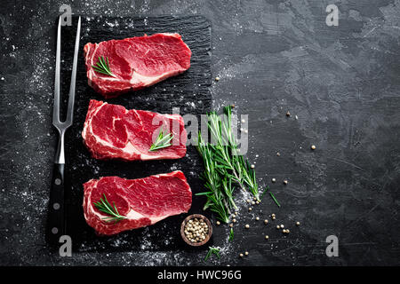 Raw meat, beef steak on black background, top view - Stock Photo