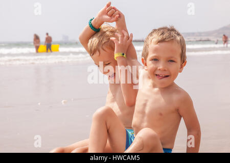 Two cute adorable little brothers boys sitting on the beach ocean sea - Stock Photo
