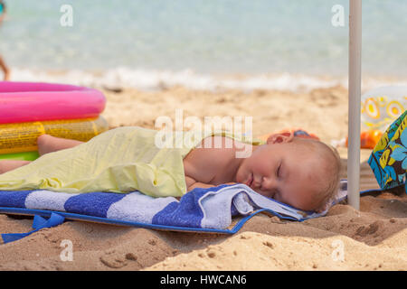 baby boy, sleeping on the beach, exhausted after fun day at the beach - Stock Photo