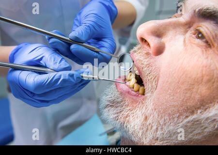 Stomatologist examining patient, close up. - Stock Photo