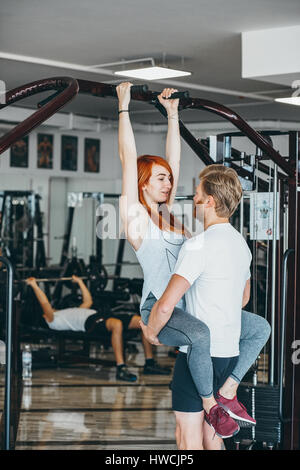 guy hepl girlfriend on training in gym - Stock Photo