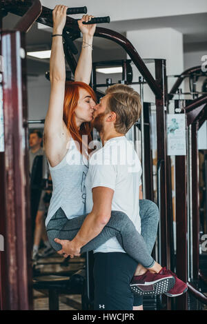 guy kiss girlfriend on training in gym - Stock Photo