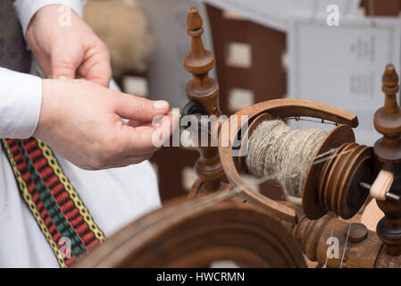 Hands of woman spinning line flax with a spinning wheel - Stock Photo