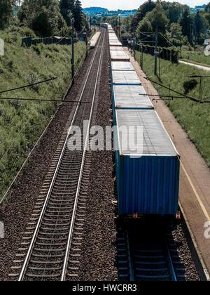 A train with goods on a section, Ein Zug mit Gütern auf einer Bahnstrecke - Stock Photo