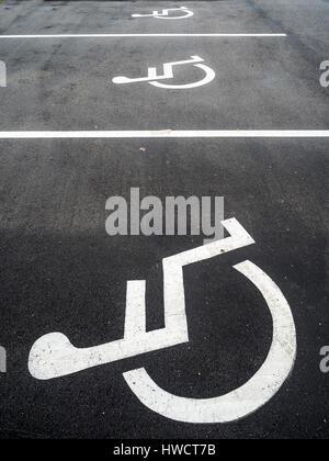 A wheel chair is right on a parking bay for disabled persons., Ein Rollstuhl ist auf einem Parkplatz für Behinderte - Stock Photo