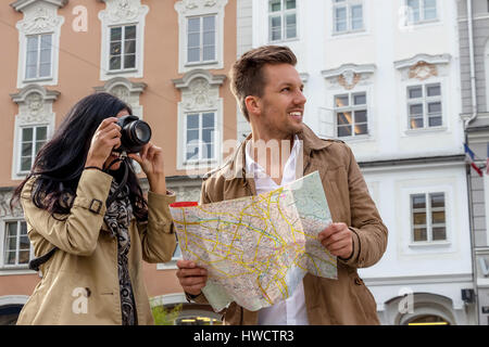 Young pair with town plan and guide with the inspection of a town on vacation, Junges Paar mit Stadtplan und Reiseführer - Stock Photo