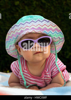 A baby with sunglasses and solar hat is well equipped against the heat in summer, Ein Baby mit Sonnenbrille und - Stock Photo