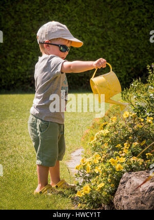 A small boy squirts the flowers on a hot day in summer with a watering can, Ein kleiner Bub spritzt mit einer Gießkanne - Stock Photo