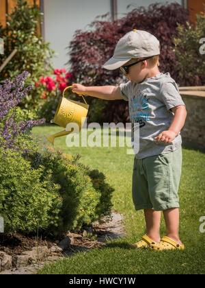 A small boy squirts the flowers on a hot day in summer with a watering can, Ein kleiner Bub spritzt mit einer Gießkanne - Stock Photo
