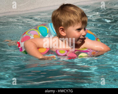 A child swims with a Schwimmreifwn in the pool and cools off on a hot summer day., Ein Kind schwimmt mit einem Schwimmreifwn - Stock Photo