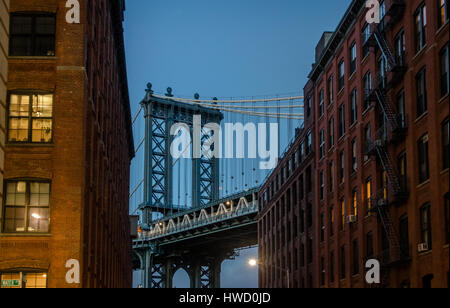 Manhattan Bridge seen from Dumbo between brick buildings on Brooklyn at sunset - New York, USA - Stock Photo
