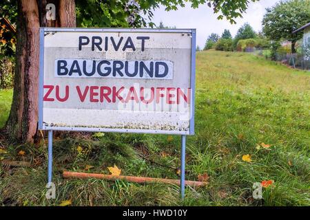 Sign with the label: To sell development site, Schild mit der Aufschrift: Baugrund zu verkaufen - Stock Photo