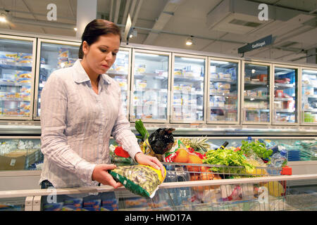 Woman goes for shopping at the supermarket, Frau geht Einkaufen im Supermarkt - Stock Photo