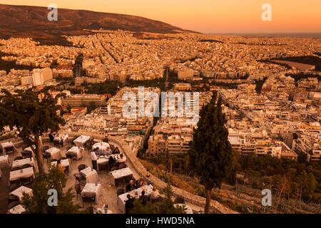 Greece, Central Greece Region, Athens, Lycabettus Hill, elevated city view with outdoor cafes, dusk - Stock Photo