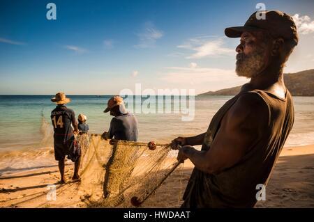 Seychelles, Mahe Island, Beau Vallon, fishermen pulling back their seine on the beach - Stock Photo