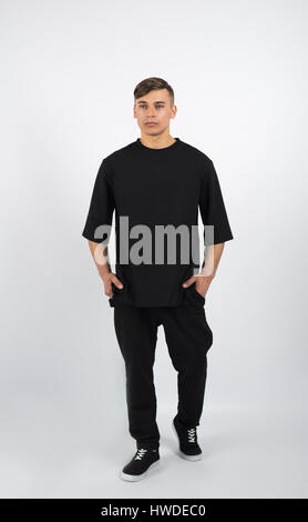 Young muscular man wearing black clothes and sneakers on white background - Stock Photo