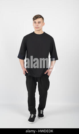 Young muscular guy wearing black clothes and sneakers isolated on white background - Stock Photo