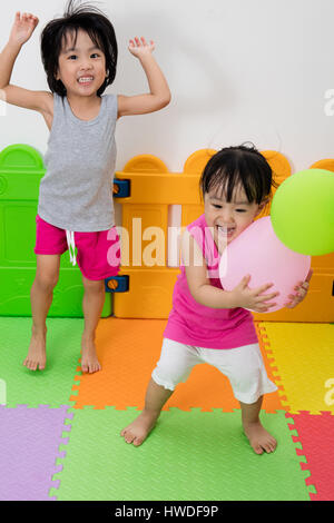 Asian Little Chinese Girls Playing with Balloons in Indoor Playground - Stock Photo