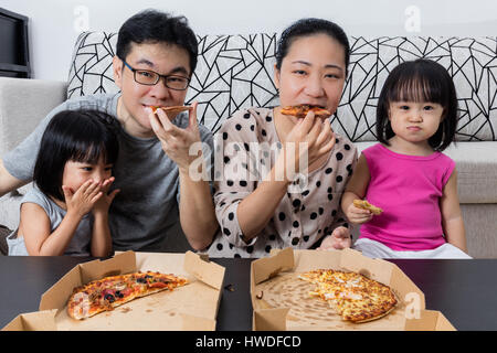 Happy Asian Chinese Family Eating Pizza Together at Home - Stock Photo