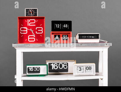 Still Life of Collection of Clocks in Variety of Styles - Clock Radio, Flip Style, and Alarm Clocks - on White Table - Stock Photo